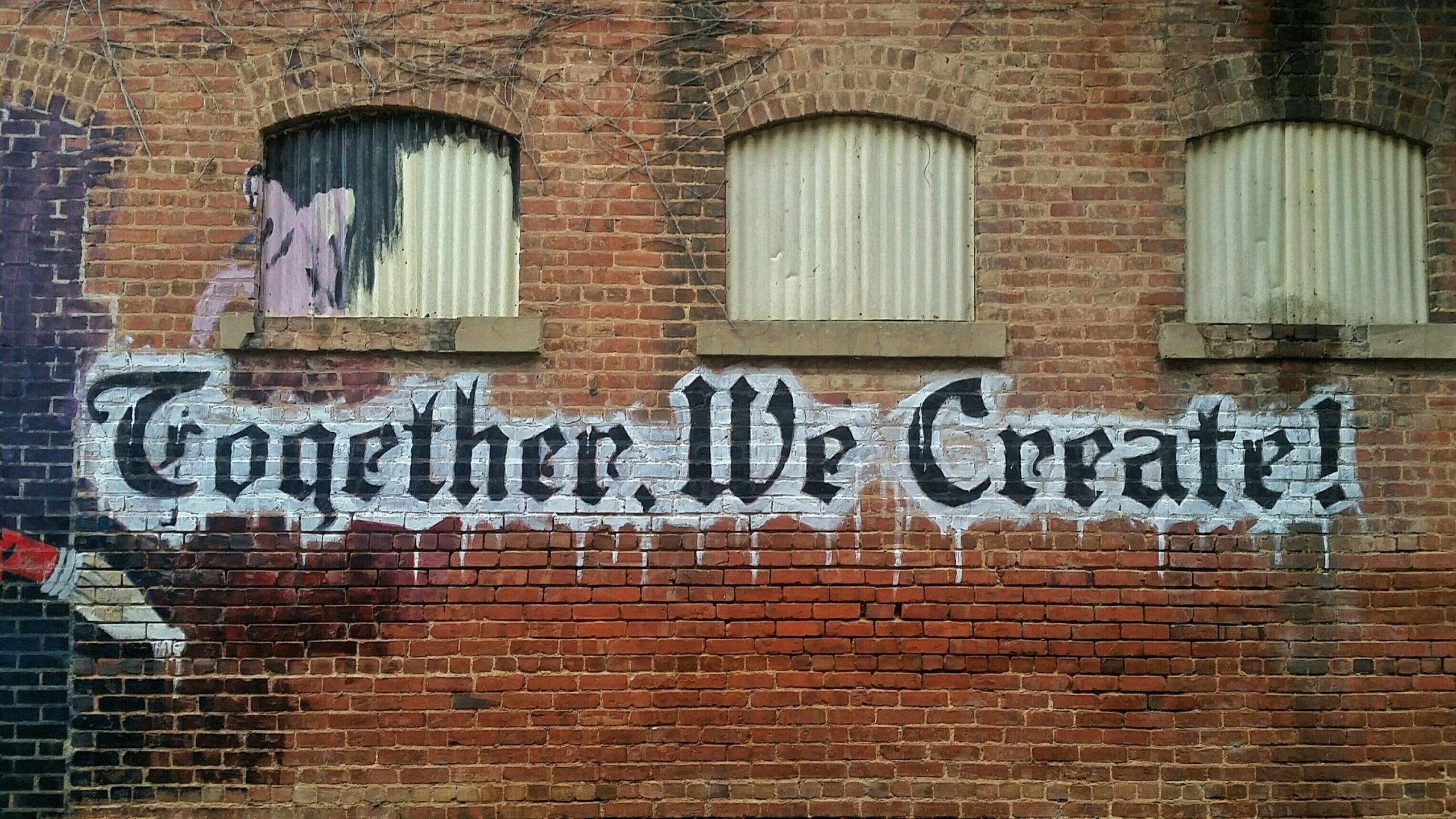 """Ziegelwand mit Schriftzug """"Together We Create"""""""